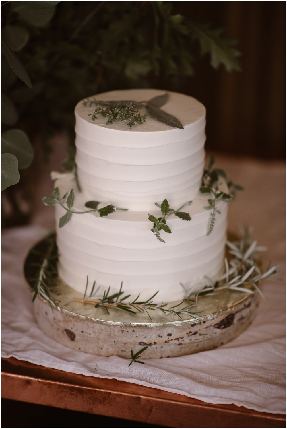 A white, meticulously frosted cake, layered with green sprigs of foliage, sits on a shiny cake plate in the Portland restaurant during the party after eloping. This was one of Lauryn and David's unquie eloping ideas they wanted to implement in their small simple wedding.