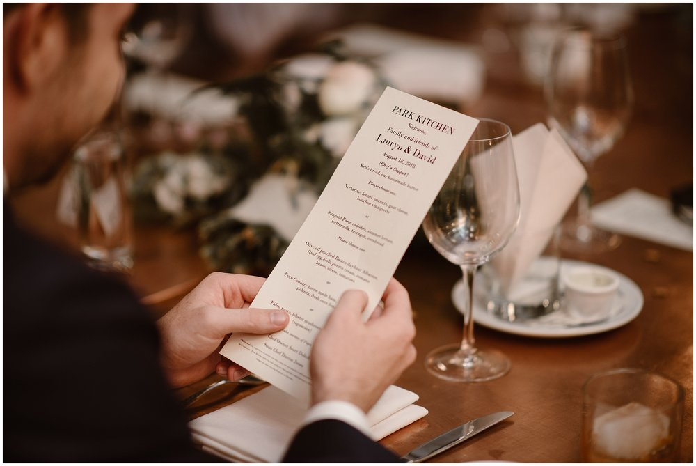 A close-up of the menu from Park Kitchen is shown in this elopement photo captured by Portland elopement photographer Adventure Instead. Lauryn and David chose to come here for their party after eloping because they wanted to eat delicious food with their family as part of their elopement ceremony.