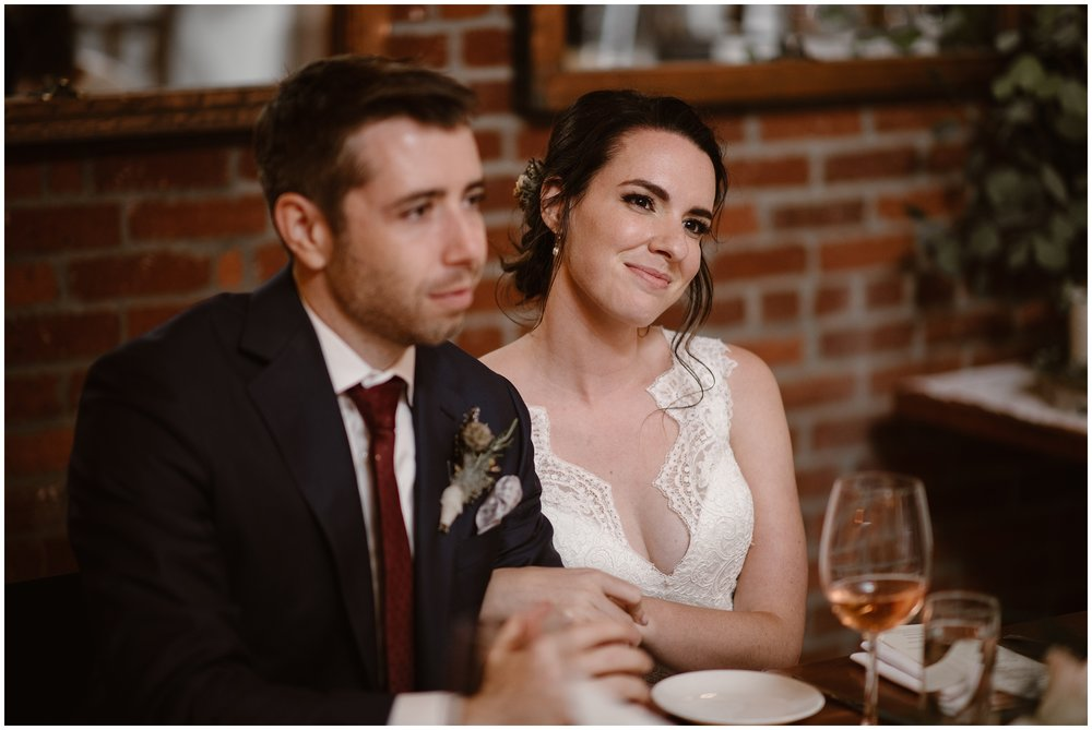 Lauryn and David link arms at the Portland restaurant during their party after eloping and look on as their family and friends celebrate their elopement ceremony.