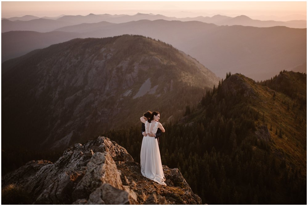 Lauryn and David hold each other close as they stand at the top of a mountain in Washington, fully dressed in their wedding attire. The sun, just rising, casts a pink and golden hue across them. IN the background, dozens of mountain ranges, tall trees, and PNW landscape can be see. This was why hiking in Washington was one of their eloping ideas—this amazing view.
