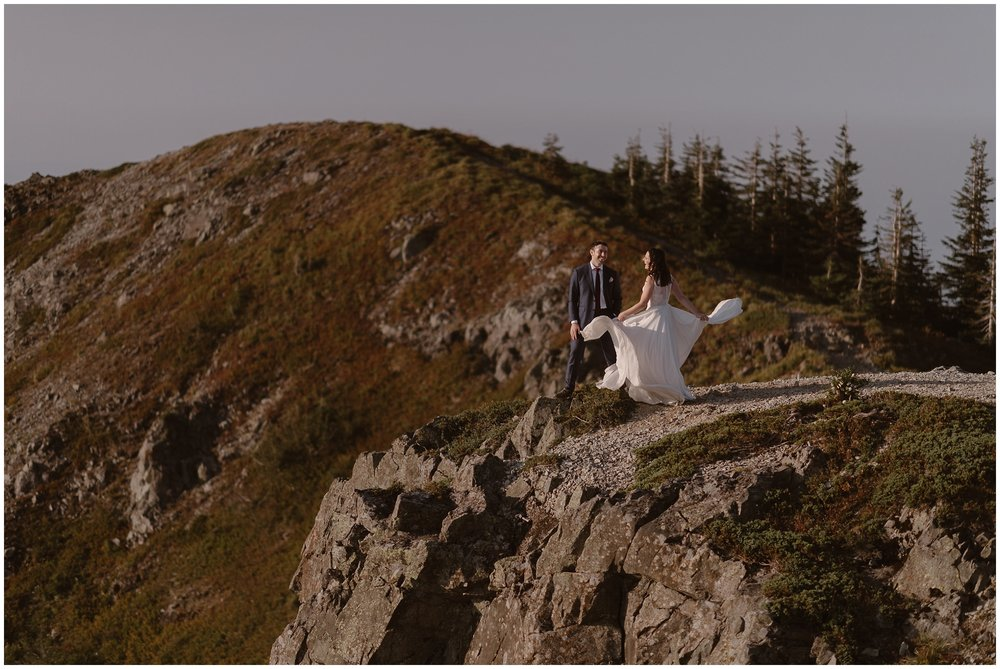 Lauryn dress dramatically flits around in the wind at the top of their epic Mount Rainier elopement spot.