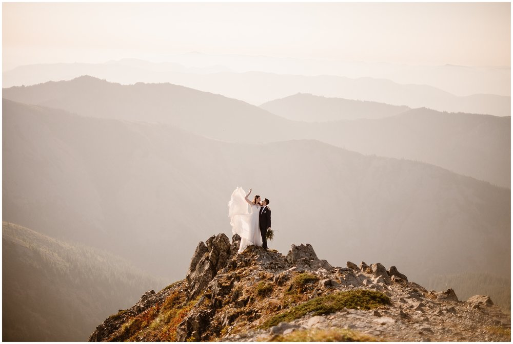 Lauryn dramatically flips her dress up in the wind at the top of the mountain during their elopement pictures. These elopement photos were captured by elopement photographer Adventure Instead.