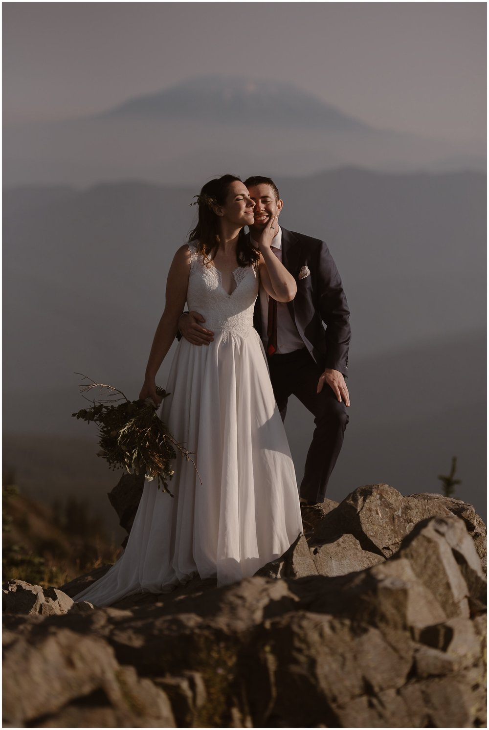 Lauryn and David stand close, holding each other, at the top of their Washington mountain for their adventure elopement photos. In the background, the top of Mount Hood peaks through a thin layer of fog.