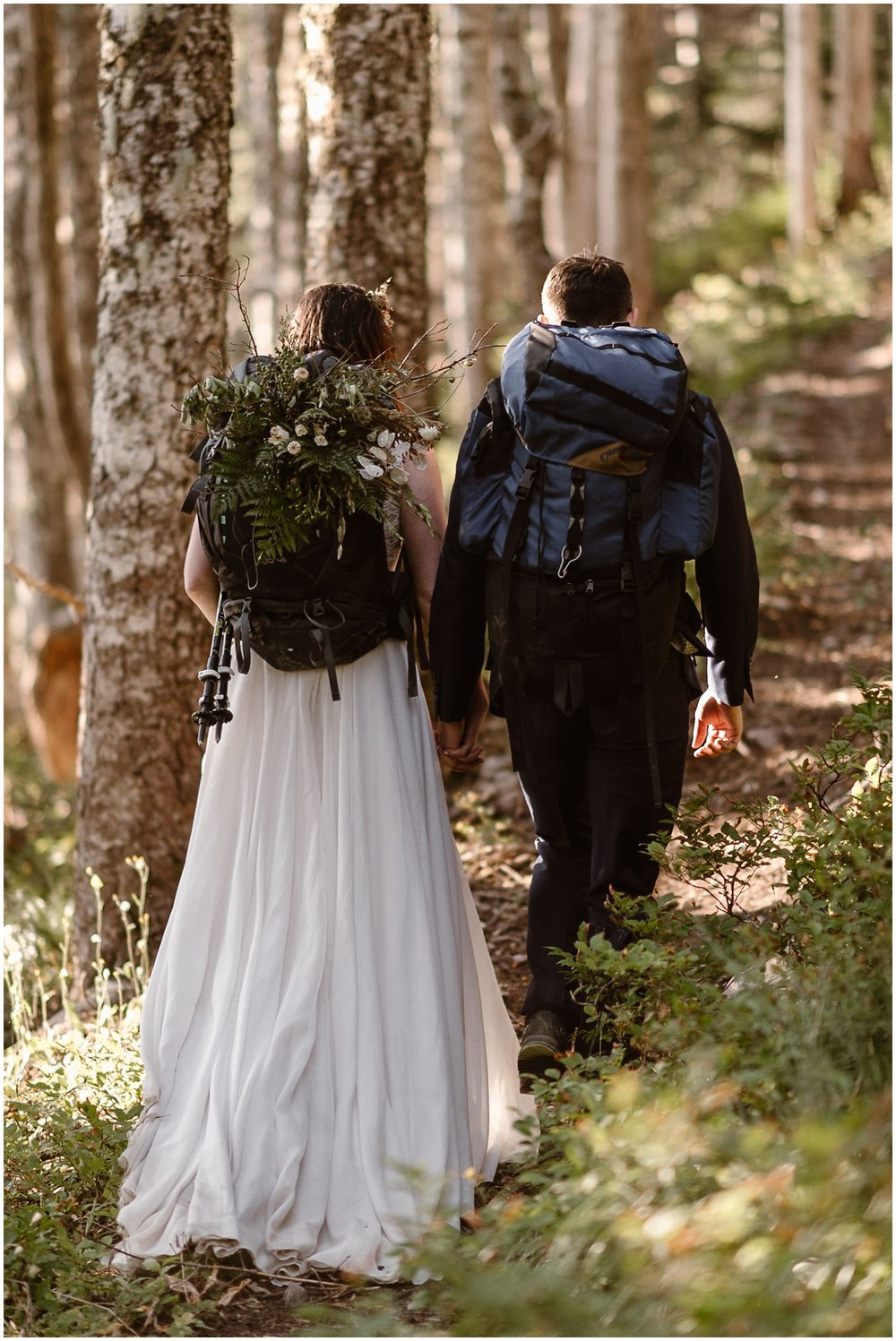 In this adventure elopement photo captured by elopement photographer Adventure Instead, Lauryn and David, the bride and groom, are seen hiking back down the mountain. Still in their wedding attire, their backpacks are loaded up with hiking gear and Lauryn's hardy hiking bouquet, one of the unique eloping ideas the couple wanted to include their elopement wedding.