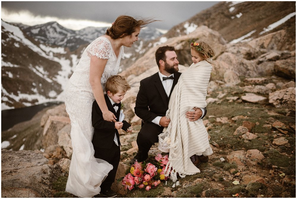 A bride and groom stand at the top of a snow-capped mountain holding onto their two children, a young boy and girl. The whole family is smiling and a bouquet of beautiful flowers lays at their feet.
