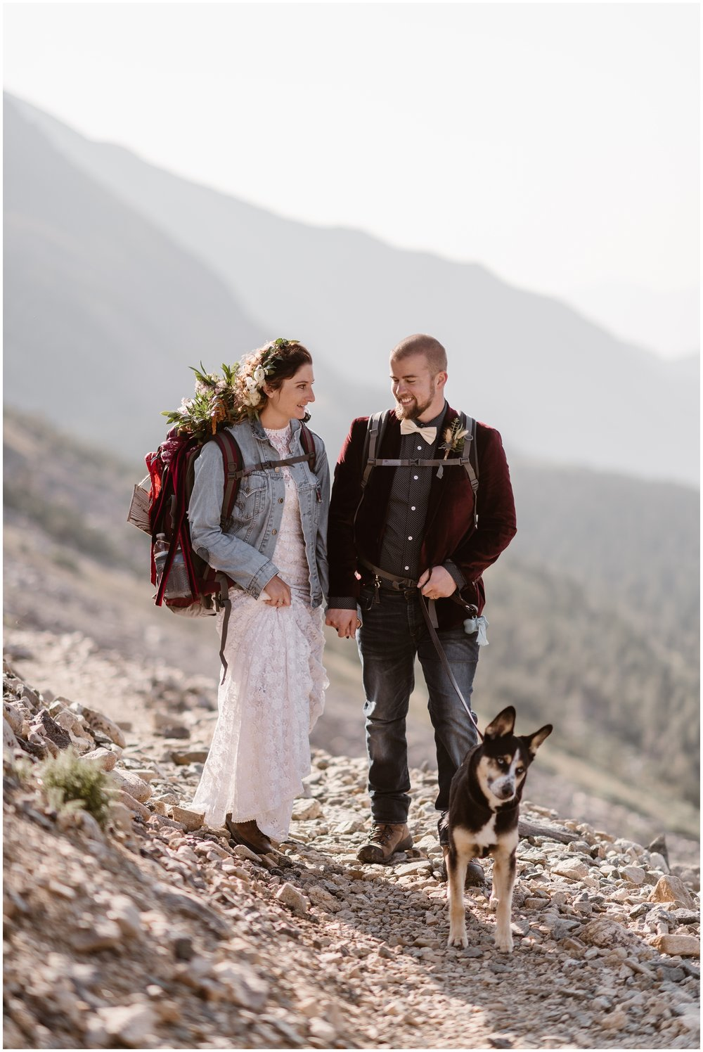 A bride and groom hike down a rocky trail with their adorable puppy. Both in their wedding attire, they're equipped with hiking gear—backpacks, hiking boots, and more. Hiking as part of your elopement wedding is one of the best elopement ideas.