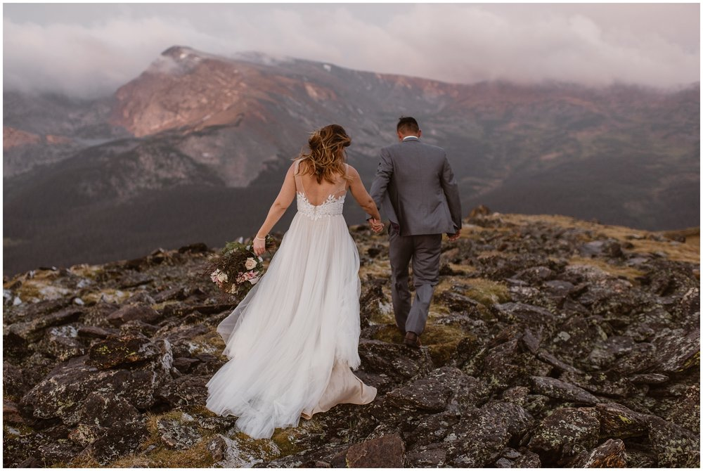 A bride and groom walk toward a dreamy mountain cast in a pink alpenglow. These elopement pictures were captured by Adventure Instead, an elopement photographer.