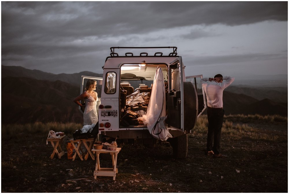 A bride and groom get ready for their adventure elopement. The two stand on either side of a Land cruiser in the wilderness as they dress to get ready for their elopement ceremony. When people ask what is eloping, often, it looks something like this.