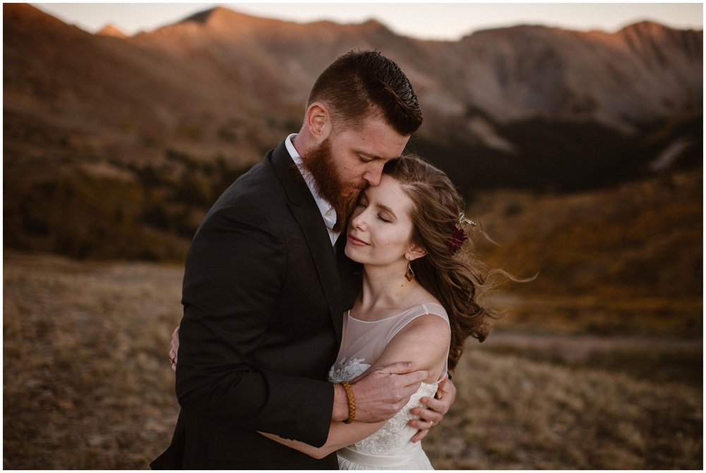 A bride and groom embrace each other with their eyes closed surrounded by nothing but beautiful mountains and a dreamy meadow. These elopement photos were captured by Adventure Instead, an elopement wedding photographer. Being totally alone on your wedding day is one of the benefits of eloping.