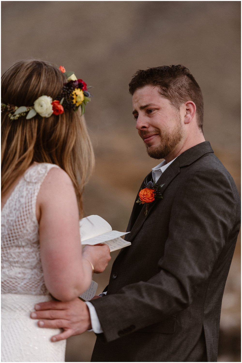 A groom touches his bride on the hip as she reads her vows to him during their elopement ceremony. He looks at her, holding back tears, as he listens to her during their small simple wedding.