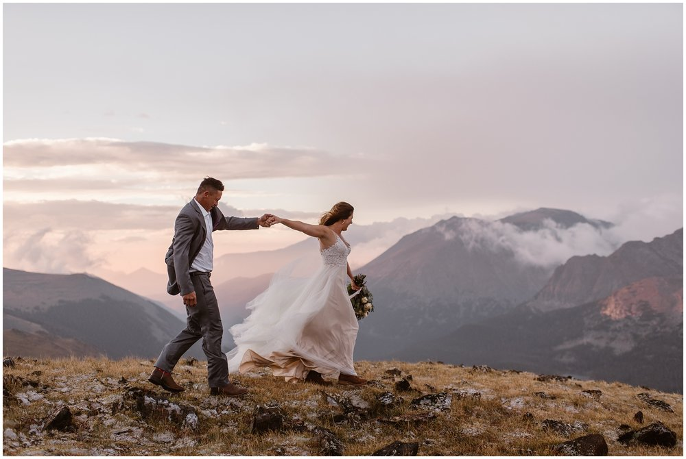 A bride leads her soon-to-be husband through an alpine-meadow at the top of a mountain. In the distance, clouds surround gorgeous, alpenglow-cast mountain peaks. These adventure elopement pictures were captured by Adventure Instead, an elopement photographer.