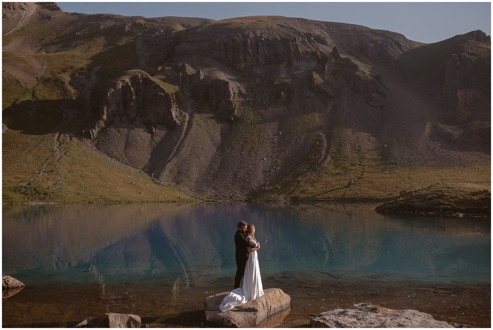 A bride and groom embrace in the distance as they stand on a rock at the edge of a gorgeous, turquoise, alpine lake. Giant green, gold, and brown mountains surround them in these elopement pictures captured by Adventure Instead, an elopement wedding photographer.