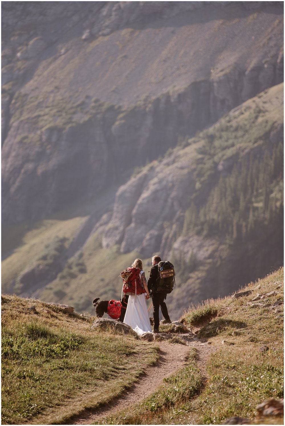 A bride, a groom, and their dog hike down a dirty path toward a rocky, grassy mountain range. Though dressed in their wedding attire, all of them (the dog included) are equipped with backpacks and hiking gear. These elopement pictures were captured by Adventure Instead, an elopement wedding photographer.