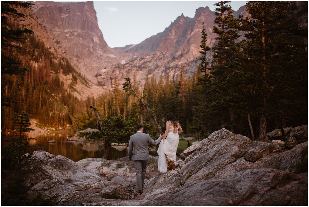 A bride and groom walk toward a gorgeous alpine lake, hand in hand. All around them, giant mountains can be seen and evergreen trees dot the landscape. These adventure elopement pictures were captured by elopement photographer Adventure Instead.