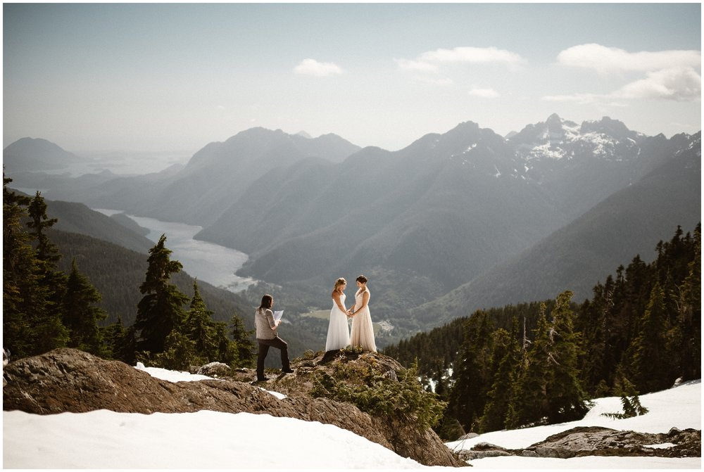 Two brides take hands as they stand on the top of a mountain during their elopement ceremony. Nearby, their chosen officiant takes them through their destination elopement ceremony. This is one of the benefits of eloping, you can choose to include an officiant in your destination wedding or not.