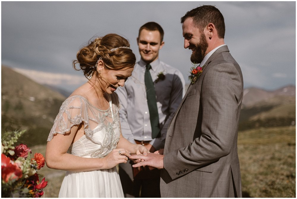 A smiling bride puts a wedding ring on her new husbands finger during their elopement ceremony. Behind them, their chosen officiant looks on. These adventure elopement photos were captured by Adventure Instead, an elopement photographer.