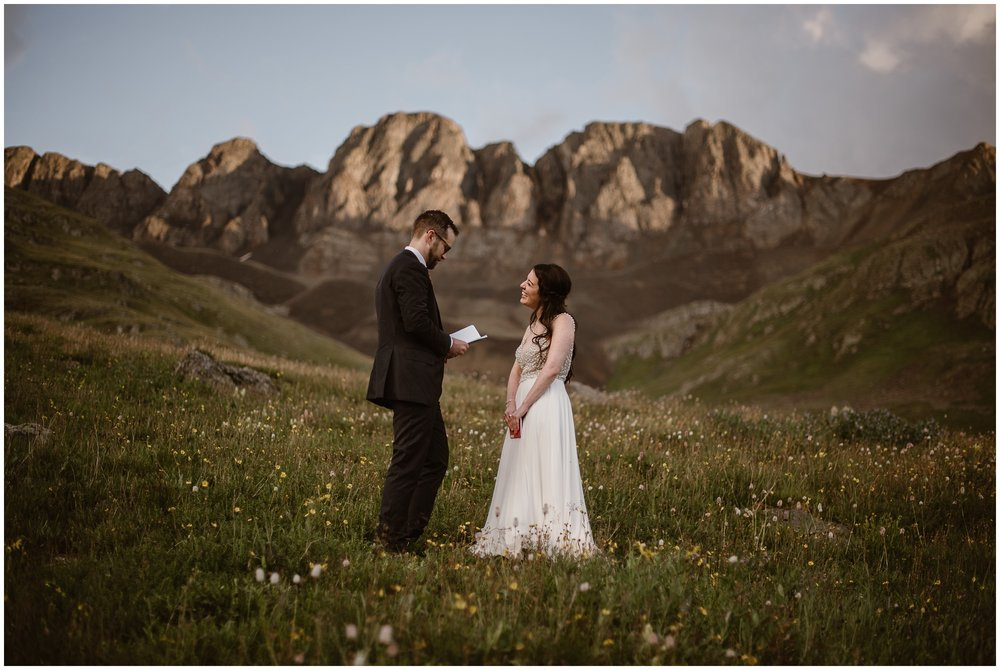 A bride and groom stand alone in an alpine meadow that's overflowing with wildflowers during their elopement ceremony. As the two read their vows—part of their self-solemnizing elopement ceremony— the bride stares at the groom and smiles. Behind them, a giant, jagged mountain range can be seen.