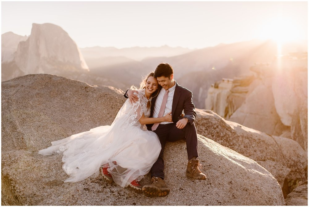A bride and groom sit on the rocks at the top of a cliff in Yosemite National Park. A Yosemite National Park elopement was the elopement wedding this couple wanted for their destination wedding. These elopement pictures were captured by elopement wedding photographer Adventure Instead.
