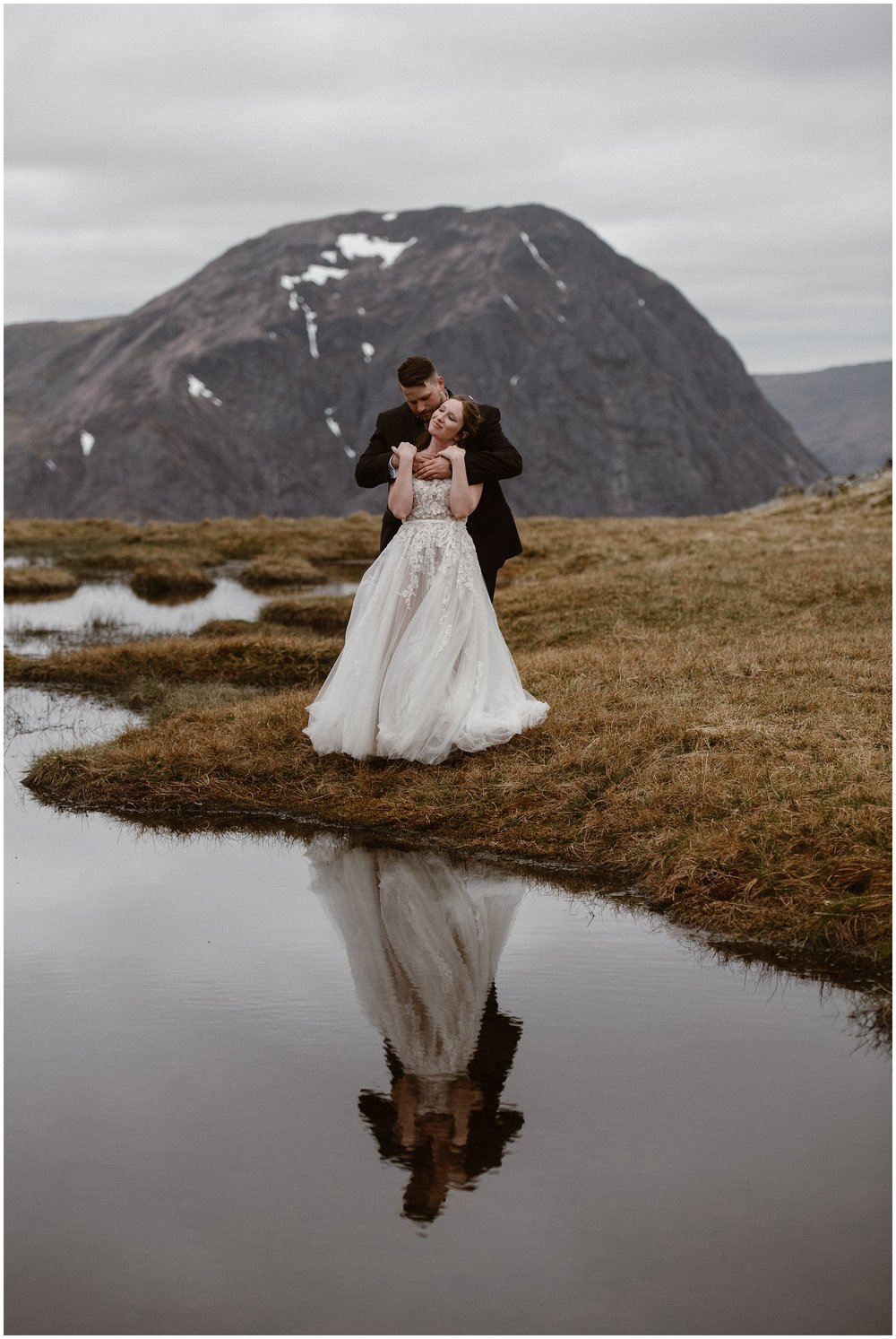 A bride and groom hold each other close at the edge of a dark, but beautiful lake, In the lake below them, the reflection of the bride and groom embracing can be seen. Behind them, a large, dome-shaped mountain can be seen. These elopement photos were captured by elopement wedding photographer Adventure Instead.