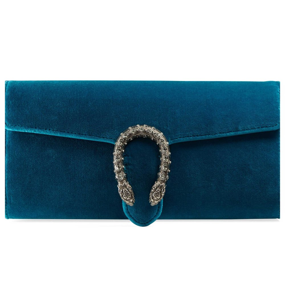 """CLUTCH:This space-saving savant of a handbag that we've been going steady with for the past five seasons is back in attack in new colors,textures, and embellishments. The Clutch or a small handbag is not only good as it requires you to keep only what is essential on your body at all times, but it also doesn't require much space for storage in your closet. This GUCCI """"Dionysus Clutch"""" with the crescent-shaped tiger-head spur is amazing for so many reasons - it's velvet, it's edgy, and the jewel tone just kills it and me.Set with glinting Swarovski crystals,this beautiful baby is available in three colors: black, wine, and azure. It's a perfect transitional piece for fall; moreover,the color and edginess of this bag make it a go-to adding a splash of color and attitude to any outfit. Get this bag here and send one my way if you wouldn't mind :)"""
