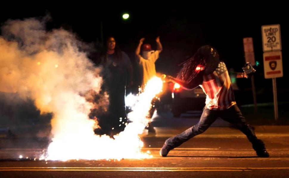 Protestors in Ferguson returning a tear gas container after tactical officers attempt to break up a group of bystanders, Aug. 14, 2014 in Ferguson, MO.
