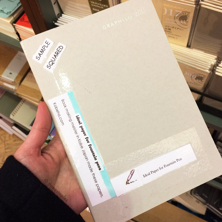 A display version of Graphilo graph notebook, with notes from the store taped on the cover. They also had a dedicated section for Midori Traveler's Notebooks (seen in the background).