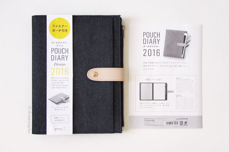 Midori Pouch Diary in dark denim (A5) and its label. It also comes in smaller, narrower format. The light button tab is leather, and the interior fabric is polyester.