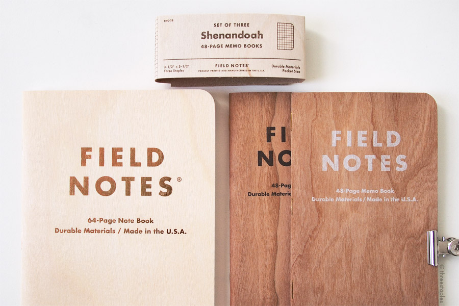 Field Notes with wood: Starbucks Roastery Edition (with birch) on the left, Cherry Graph and Shelterwood on the right, both with cherry wood. The Shenandoah belly band on the top also features birch veneer.