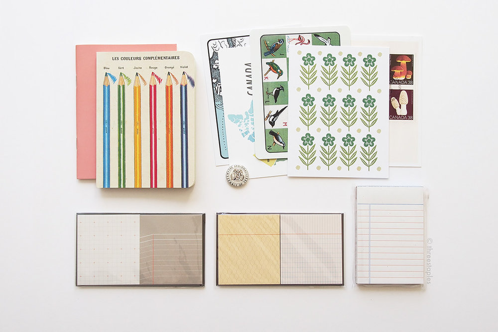 Sticky notes and peach notebook by  Paperways , mini letterpressed note pad by  Bison Bookbinding & Letterpress , various postcards by  The Regional Assembly of Text , and graph grid notebook with color pencils on the cover by  Cavallini Papers & Co .