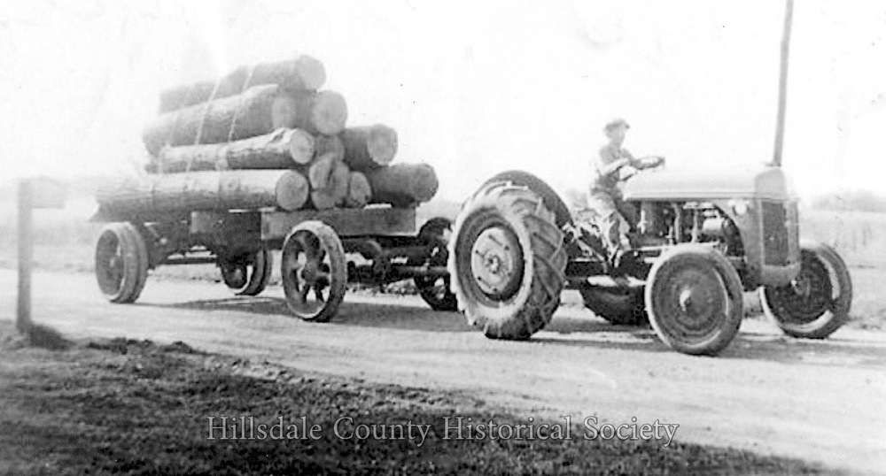 a young george woodard hauls logs to be used for lumber in bankers.