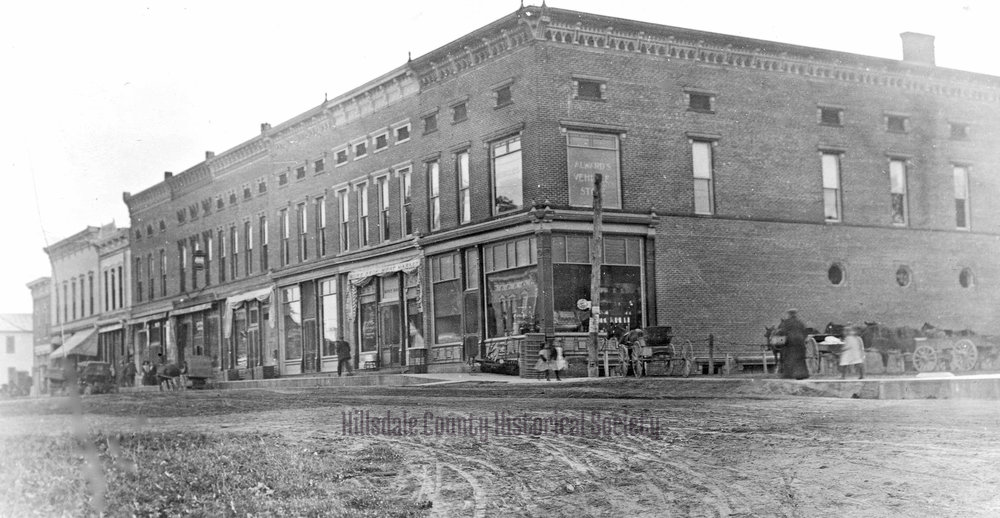 "The west side of main Street, with Alwards's Vehicle Store on the corner. All the ""vehicles"" appear to be horse drawn."