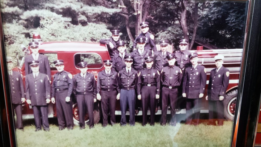 volunteers from the early 1960s. L to R: George Whitson, Gabby Gaberdiel, Fletcher Bishop, (unknown), (unknown), Jim Taylor, Warren Taylor, Ed Minihan, Delbert Ellis, Chief Harry Payne. Behind on the left is Tom Bates. The man standing on the right, higher than the others, may be Nick Ferro. The others are unknown.