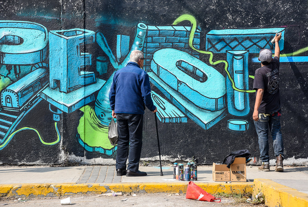 Neighborhood resident observing 'Peyote' painting for the ' Mi Nuevo Barrio Art Festival' in the colony of Nueva Vallejo, MX.