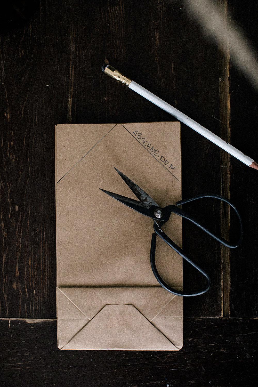 4. Schneide jetzt die Ecken des Tütenstapels ab. Umso dicker das Papier, desto schwieriger lässt es sich schneiden. Wenn du magst, kannst du auch Halbkreise in die Seiten schneiden. Das ergibt ein schönes Muster.