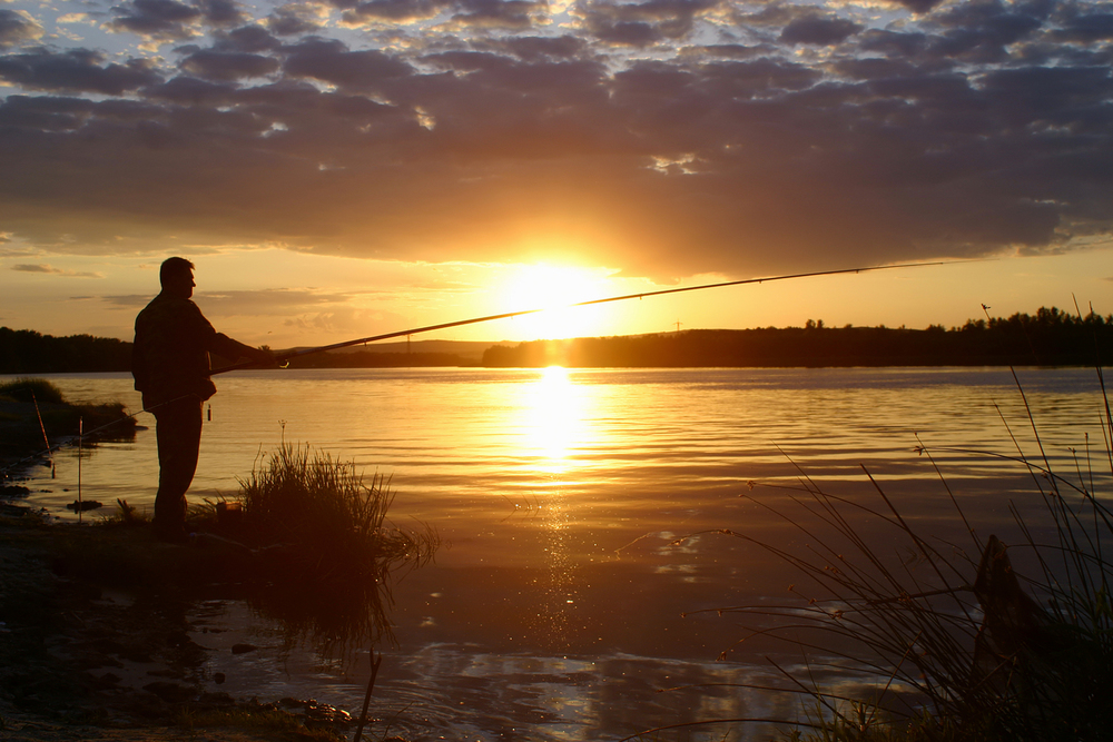 Fisherman casting from shore at sunset