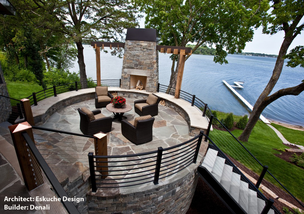 Mountain Modern round stone patio overlooking lake by Eskuche Design