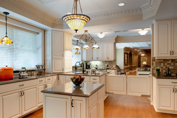 White kitchen for senior care with square cafe doors and center island