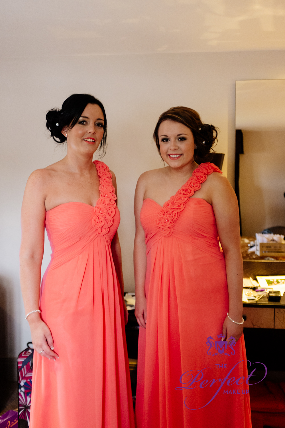 The gorgeous bridesmaids in their coral dresses.