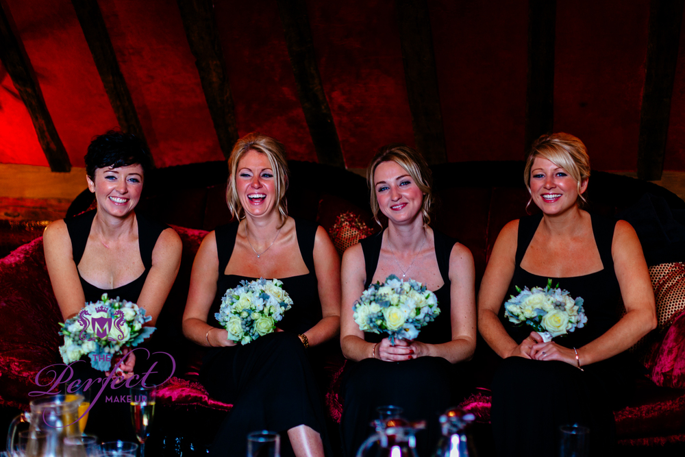 The lovely bridesmaids in full make up and wearing long black dresses.