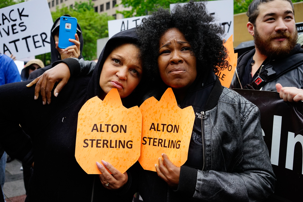 Two women hold each other in the crowd at the vigil for Alton Sterling in Seattle, Wa.