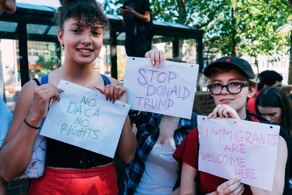 Students pose with signs at a rally supporting DACA recipients.