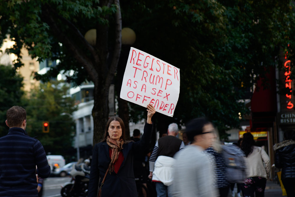 A woman holds a protest sign at the 'Cancel Kavanaugh' rally opposing the nomination of the new Supreme Court justice