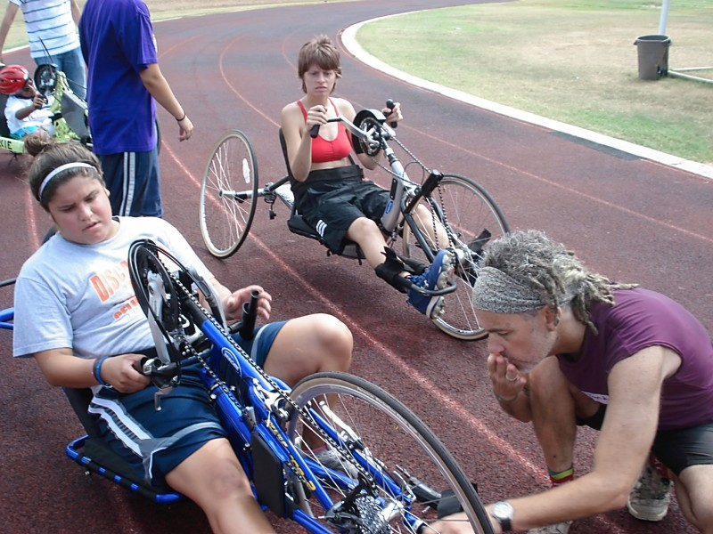 Randy signs (ASL) at a Texas Rowing For All introduction to hand cycling for deaf participants.