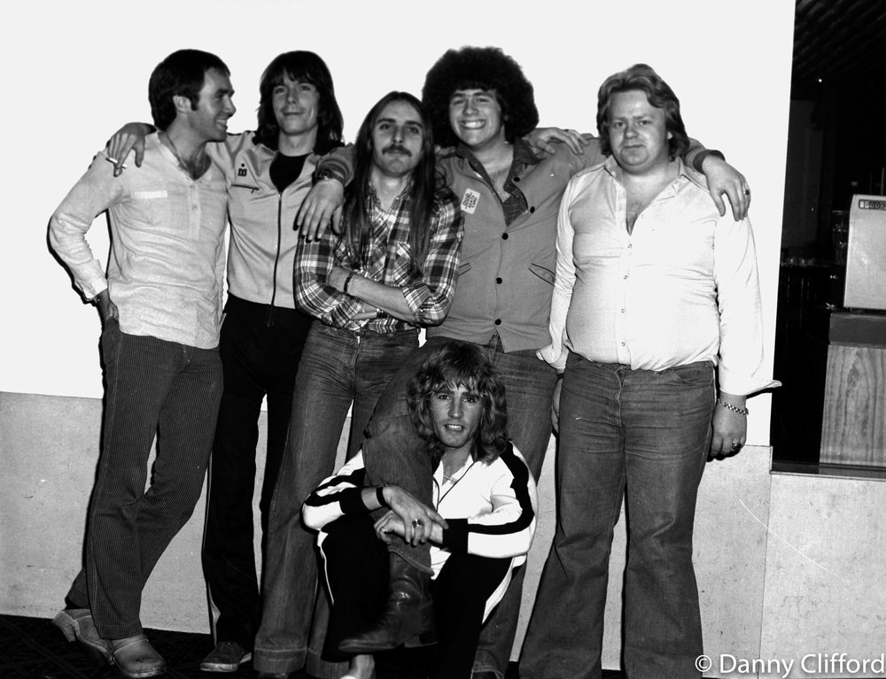 Me with most of the band on the road in the early days.. Yes, I did have hair! Thats me with the fro! L-R Bob Young, Andrew Bown, John Coghlan, Danny Clifford, (Quo's driver) and sitting on the floor with his arms round my leg is the wonderful Rick Parfitt..