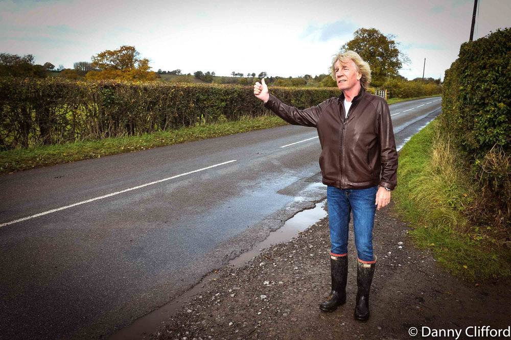 Rick pretending to hitch hike whilst we were out in the English countryside. Quo were promoting a beer & cider that they had put their name to. We were on an farm at the time when we shot this.