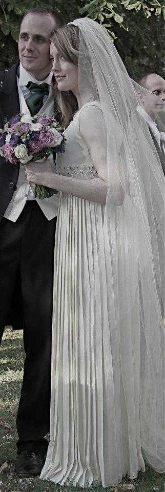 """I got married recently in one of your fab dresses!! Many thanks for everything and in particular to the alteration team who worked wonders on the dress so that I would fit into it!"" – Susan Doran Susan wears- 1960's dress with detailed appliqué waistband and pleated skirt teamed with a full-length sheer tulle veil."