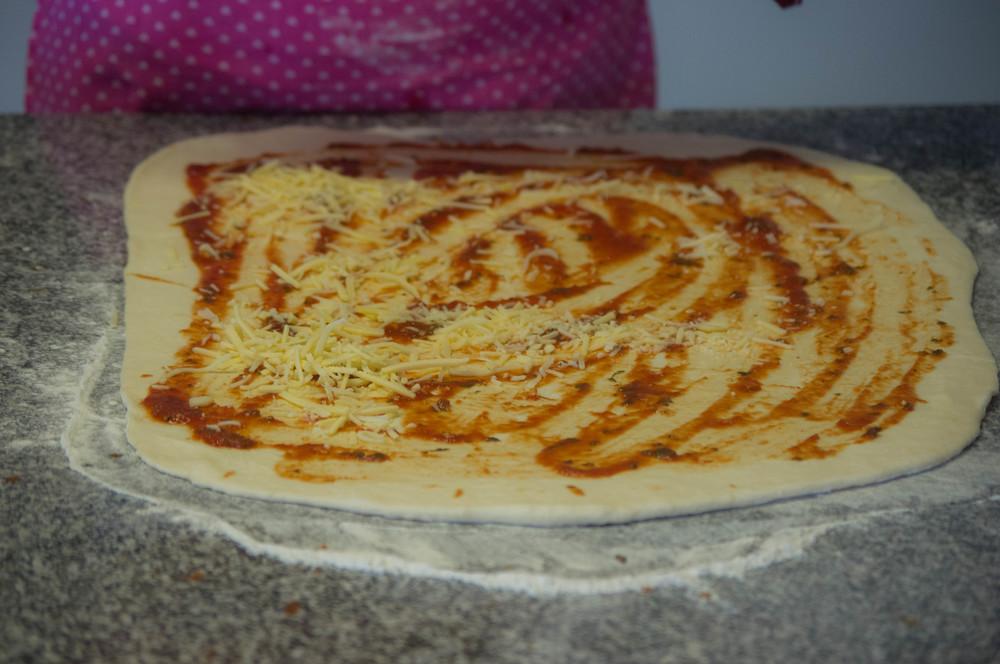 Estira la masa, untala con la salsa y agrega el queso