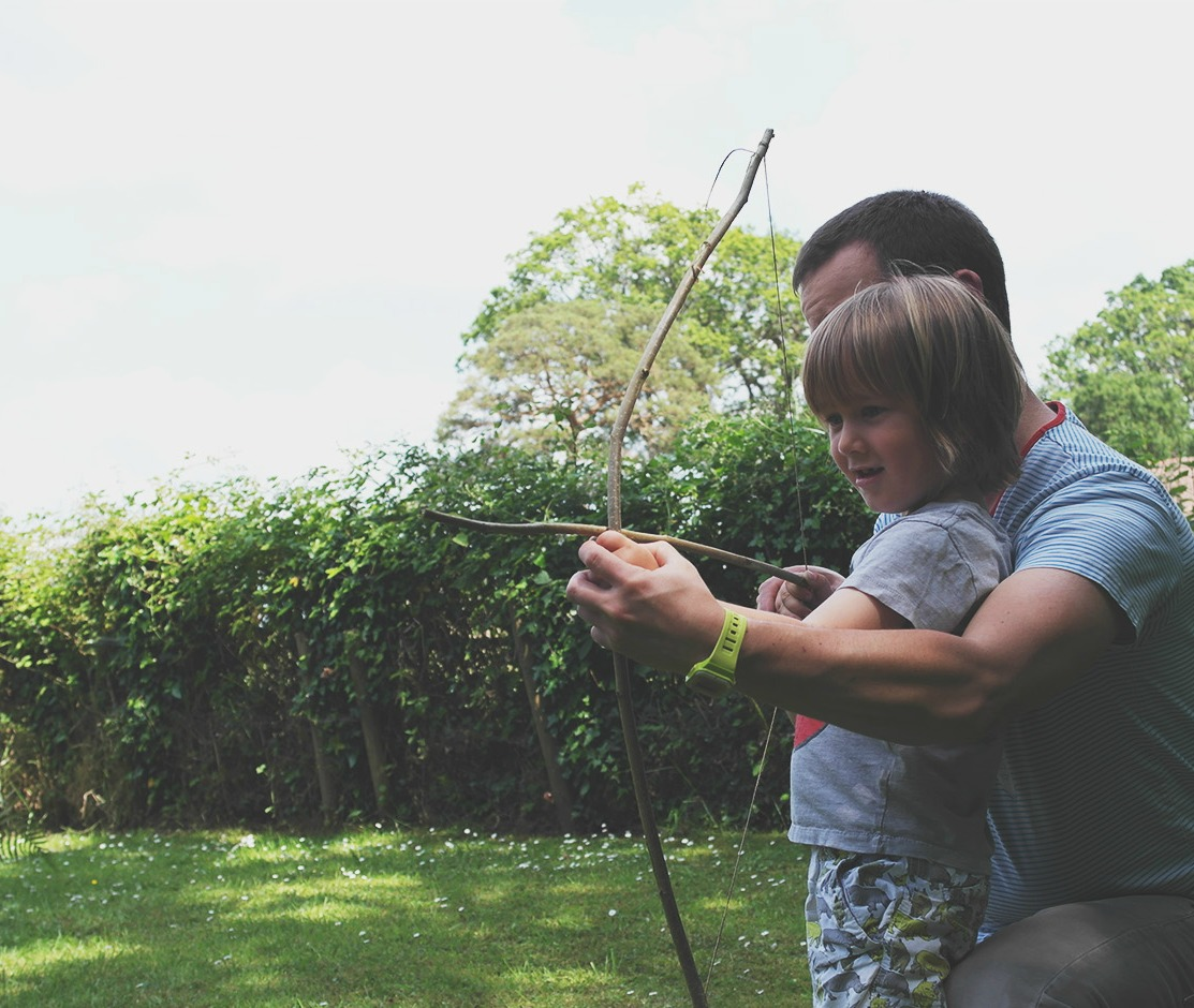 Father and son firing an arrow from a homemade bow