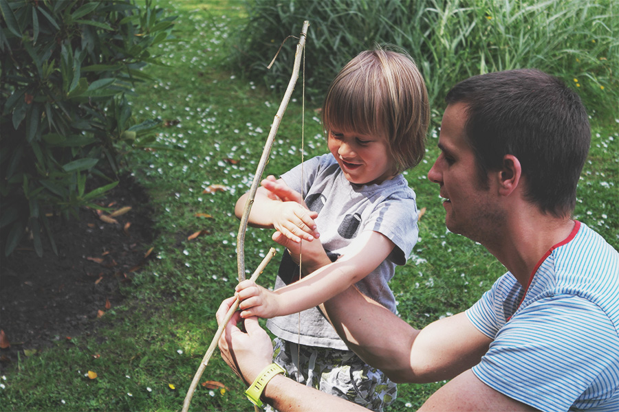 Father shows son how to fire bow and arrow