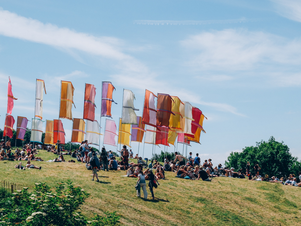 Glastonbury 2015 in Photos: Festival goers relaxing beneath the flags